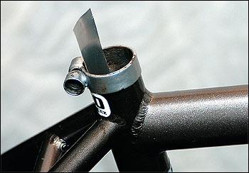 Pásek vložíme mezi sedlovou trubku a sedlovku